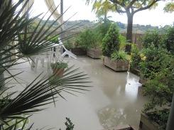 Davant l'estança dels petits, el porxo pavimentat i diferenciat del paviment de terra