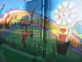 On hi havia una lona tapant la visió delpati, ara hi ha un grafiti que dóna obertura a l'interior de l'escola.